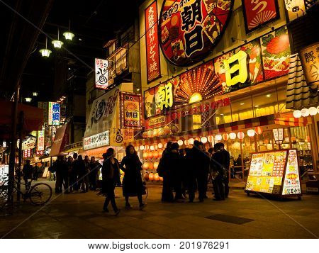 OSAKA, JAPAN - JULY 18, 2017: Unidentified people buying and walking on dowtown Osaka at night in Osaka, Japan.