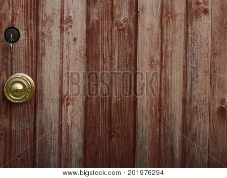 A section of an old wooden door including the doorknob and a dangling set of keys.