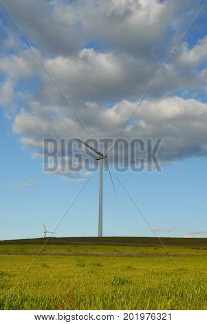 A windmill located in central Kansas on a semi cloudy day.