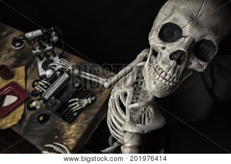 Human Halloween Skeleton with a Typewriter Telephone and Cookie On A Plate