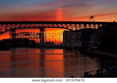 Pink and golden summer sky after sunset over the Cuyahoga River in Cleveland Ohio
