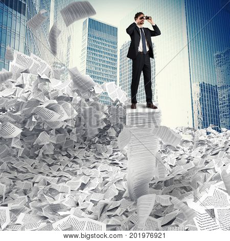 Man surrounded by paperwork on a stack of paper looks far with binocular