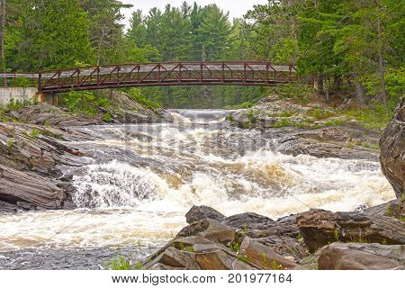 Hiking Bridge over a the Aux Sables River in Chutes Provincial Park in Ontario Canada