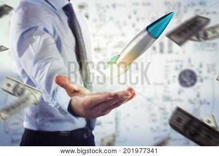 Businessman holding a small rocket. Startup working enterprise concept