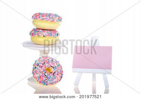 Colorful frosted donuts piled on a small pedestal with one donut below small pink easel next to it for message or text isolated on white background. National donut day theme or birthday party