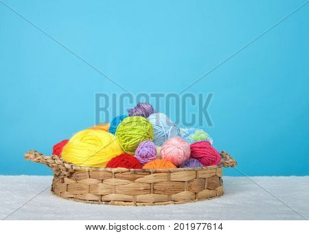 Brown basket full of colorful balls of yarn for knitting and or crocheting yarn crafts sitting on a sheepskin blanket with blue background