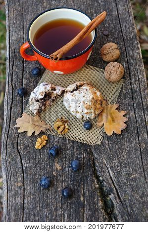 Romantic autumn still life with cookies, cup of tea, walnuts, blackthorn berries and oak leaves
