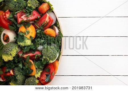 most useful vegetables are broccoli, onions, garlic, tomatoes, carrots sliced with greens in a black plate. View from above, a great place for text