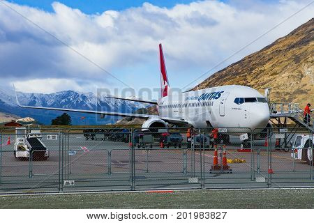 QUEENSTOWN NEW ZEALAND - SEPTEMBER62015 : qantas airline plane loading passenger belonging in queenstown airport south land new zealand