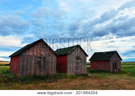 An image of three red wooden granaries against a dramatic cloudy sky.