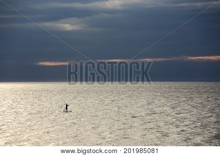 silhouette of woman - SUP surfer alone at sea in the twilight