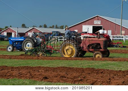 DUNDAS, PRINCE EDWARD ISLAND, CANADA - 25 Aug: Competitors plow withantique tractors at the PEI Plowing Match and Agricultural fair on August 25, 2017 in Dundas, Prince Edward Island.