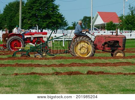 DUNDAS, PRINCE EDWARD ISLAND, CANADA - 25 Aug: Competitors plow with amtique tractors at the PEI Plowing Match and Agricultural fair on August 25, 2017 in Dundas, Prince Edward Island.