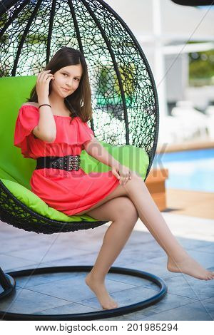 pretty teenage girl relaxing on a lounger outdoors.