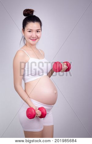 Pregnant exercises concept.A portrait of a Beautiful asian pregnant woman doing light exersice by using dumbell at home.