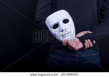 Mystery man holding white mask in the back. Anonymous social masking concept.