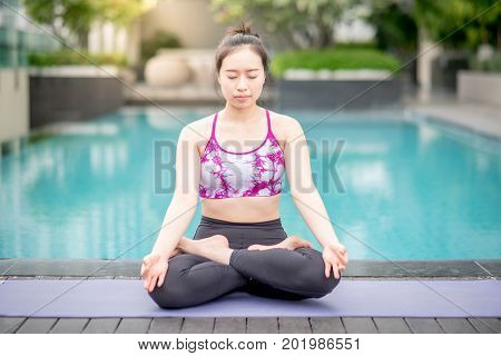 Beautiful young Asian woman doing yoga exercise with padmasana posing or lotus position pose near swimming pool. Healthy lifestyle and good wellness concepts