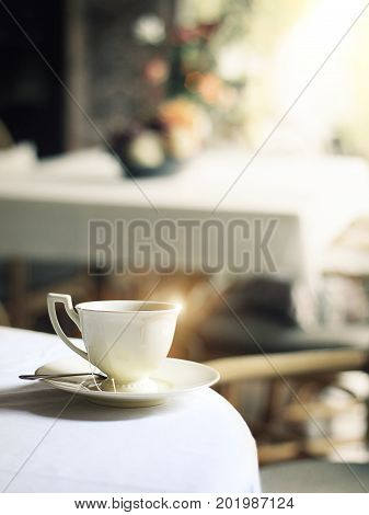 cup of hot steam coffee on table in cafe with morning glistening light reflect
