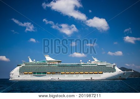 Luxury cruise ship sailing from port. Big cruise ship in the sea with beautiful blue sky background. Beautiful summer seascape poster for advertise. Holiday vacation lifestyle on cruise.