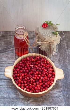 Very ripe cowberries in a bowl on the table and cranberry drinks and jam. On a wooden background, space for text.