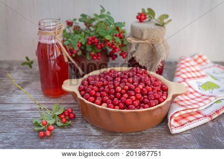 Very ripe cowberries in a bowl on the table and cranberry drinks and jam. The bouquet of sprigs of cranberries in a pot. On a wooden background, space for text.