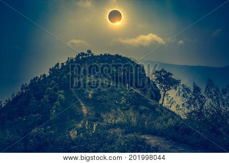 Amazing scientific natural phenomenon. The Moon covering the Sun. Total solar eclipse with diamond ring effect glowing on sky above view point on the top of mountain serenity nature in forest. Cross process.