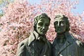 Brother Grimm sculpture in Kassel, Germany with blooming tree poster