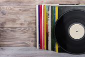 Retro styled image of a collection of old vinyl record lp's with sleeves on a wooden background. Copy space. poster