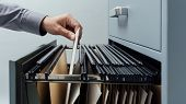 Office clerk searching for files into a filing cabinet drawer close up business administration and data storage concept poster
