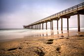Overcast cloudy day over Scripps pier Beach in La Jolla, California at the end of Summer poster