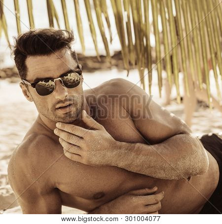 Muscular man on the beach ,fashion style image
