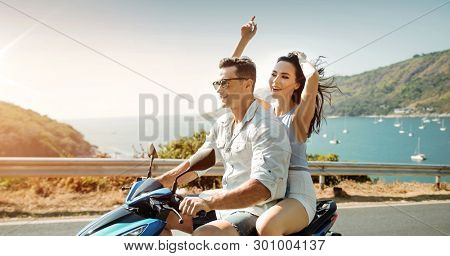 Attractive young couple riding a scooter