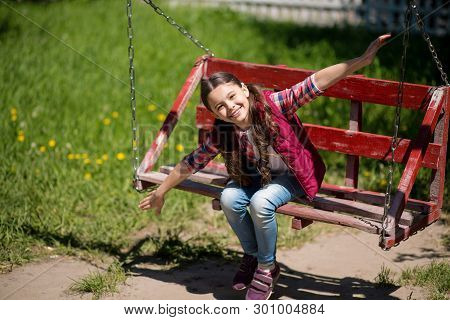 Smiling Little Girl With Long Pigtails Is On The Swing In The Park.she Is Smiling While Looking An T