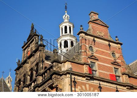 The external facade of Oude Stadhuis (Old Town Hall, 16 century) with its carvings and turret, and the clocktower of Grote of Sint Jacobskerk in the background, The hague, Netherlands poster