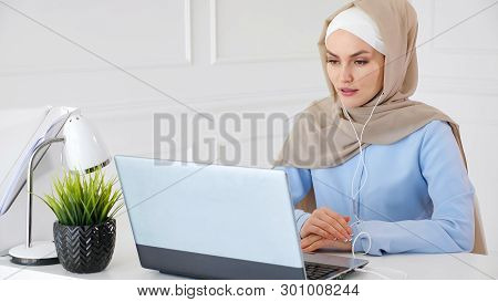 Portrait Of Young Muslim Woman In Hijab And Traditional Clothes Is Learning English In Earphones Onl