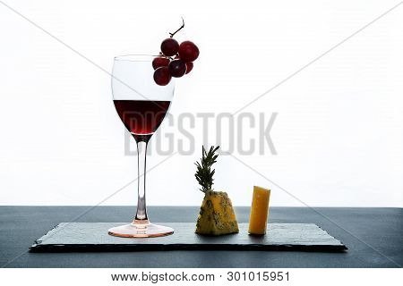 Glass Of Red Wine Garnished With Grape And Pieces Of Savory Cheese