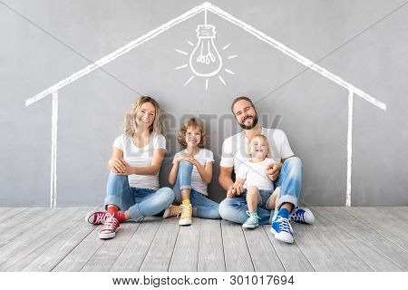 Happy Family With Two Kids Playing Into New Home. Father, Mother And Children Having Fun Together. M