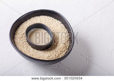 Tahini Sauce And Sesame Seeds In Black Bowls On White Background. Natural Paste Made From Sesame See