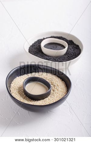 Black Tahini And White Tahini Sauce In Bowls On White Background. Natural Paste Made From Sesame See