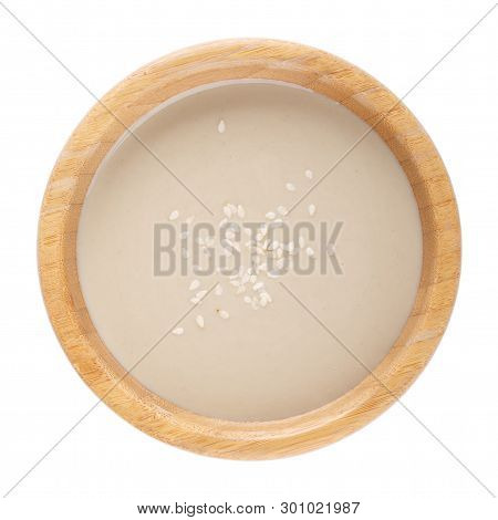 Tahini Sauce In Wooden Bowl Isolated On White Background. Natural Paste Made From Sesame Seeds. Top