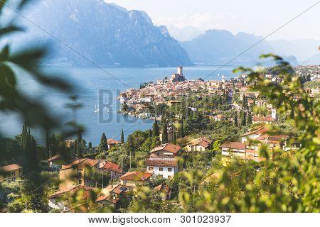 Idyllic Coastline Scenery In Italy: Blue Water And A Cute Village At Lago Di Garda, Malcesine