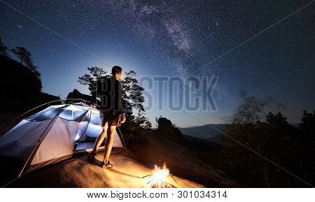Back View Of Tourist Man Resting On Rocky Mountain Top Beside Camp, Bonfire And Tent At Summer Night