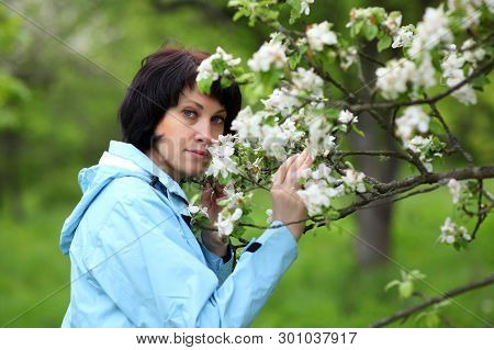 Eautiful Mature Woman Posing For The Camera In The Spring Garden. The Girl Enjoys The Flowering Of A