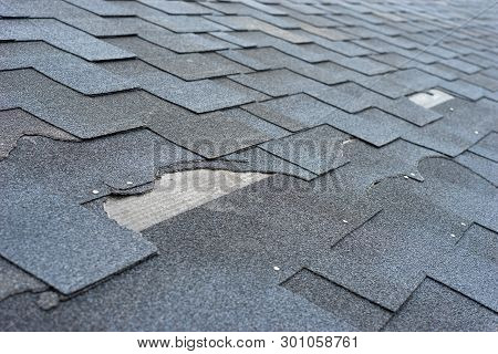 Сlose Up View Of Asphalt Shingles Roof Damage That Needs Repair.