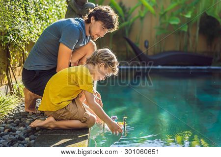 Dad And Son Playing With A Boat In The Pool