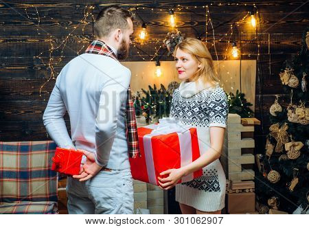 Man Hipster Give Gift To Girl Christmas Decorations Background. Surprise For Sweetheart. Merry Chris