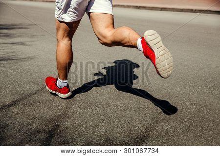 Feet Man Runner Running Street. Shadow Runner On Gray Asphalt