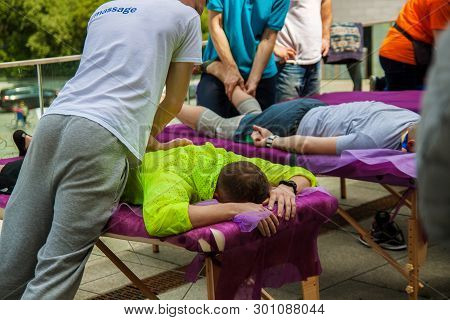 Sports Massage. Massage Therapist Massaging Shoulders And Legs Of Athletes, Working With Trapezius M