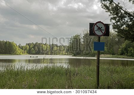 Swimming Prohibited. Lake, A Large Water Reservoir Amidst Forests. The Shores Overgrown With Tall Gr