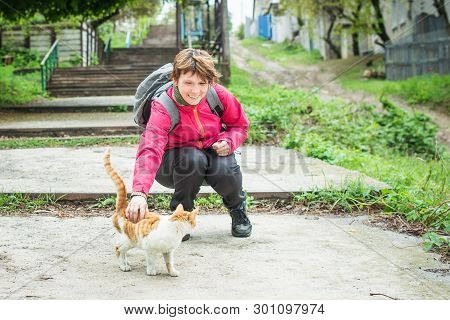 Smiling woman stroking a purring cat on the street. Auburn and white color. Homeless animal. poster